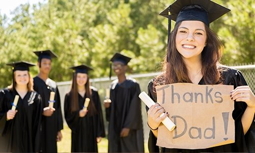 "Graduate holding a ""Thanks Dad!"" Sign"