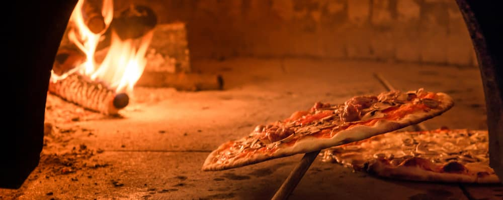 Pepperoni pizza being taken out of a brick oven