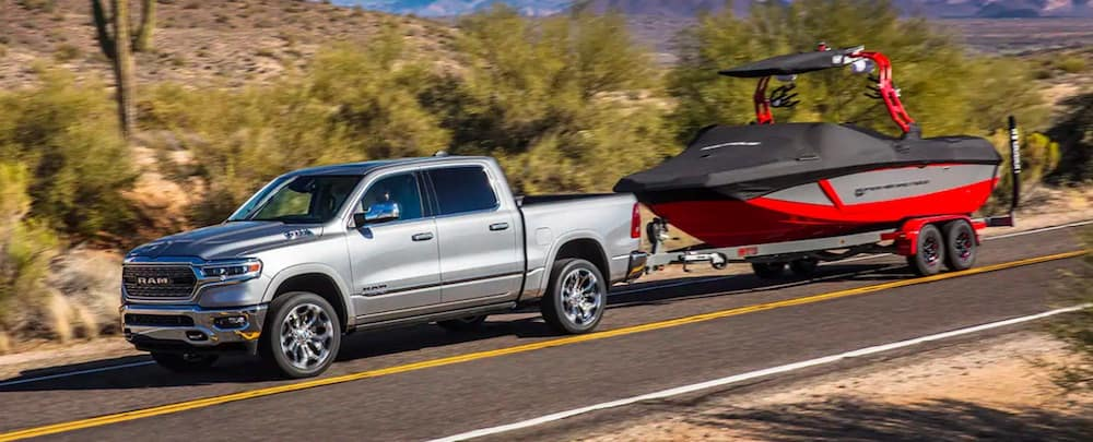 Silver All-New 2019 RAM 1500 towing a red boat
