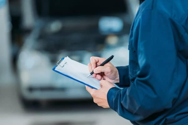 mechanic filling out service paper on clipboard