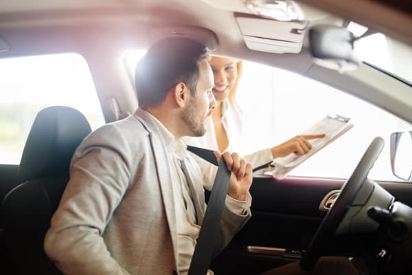 dealer shows man papers as he sits in car