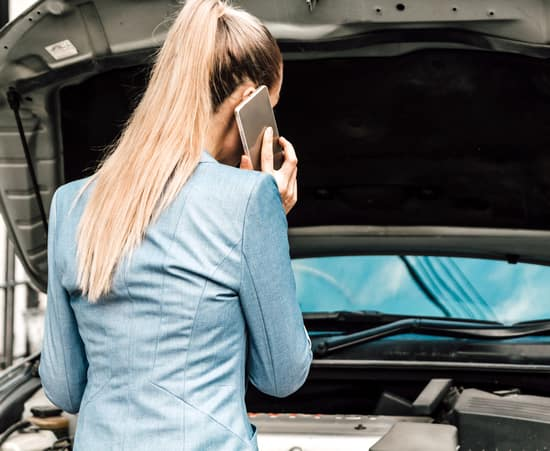 Woman calling for assistance with broken down car engine