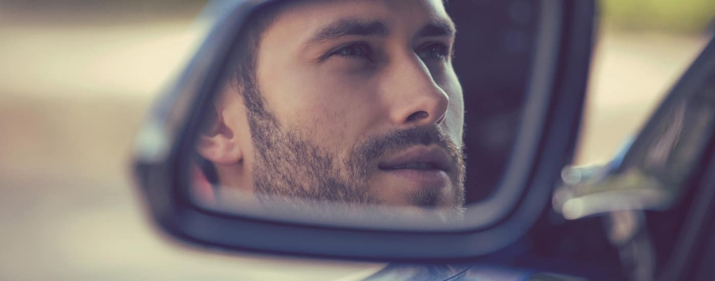 Man looking out of drivers side car mirror
