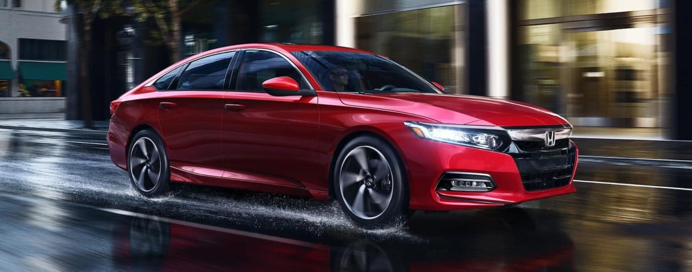 Red Honda Accord driving through city streets