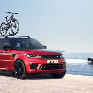 2018 Land Rover Range Rover Sport driving on the beach with bike mount accessory