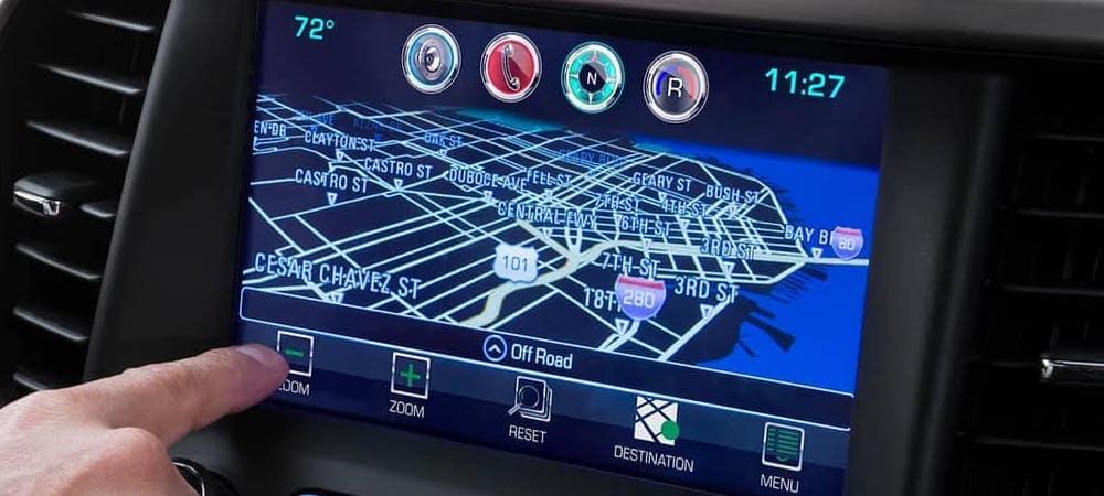 Hand using 2018 GMC navigation touchscreen