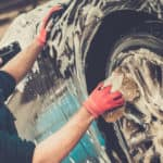 man washes wheel of vehicle