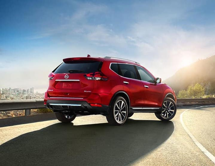 Red 2018 Nissan Rogue driving toward the sun