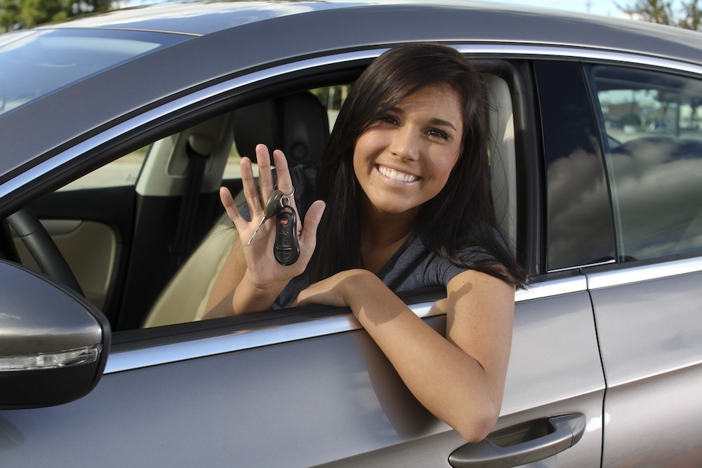 A woman holding keys and smiling from the driver seat of her newly bought used car
