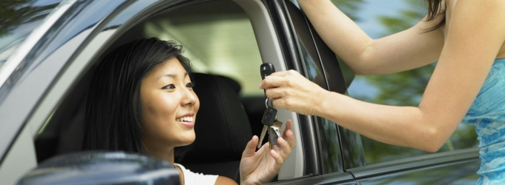 A woman being handed car keys while she sits in the driver's seat.