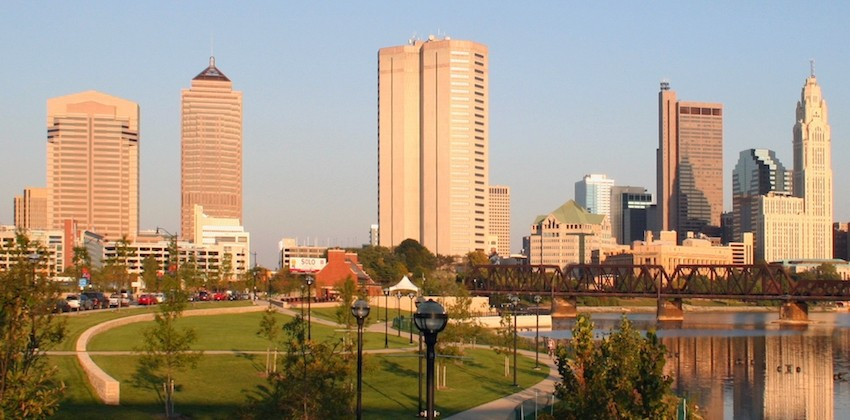 A park against a river with the Columbus skyline against a blue sky
