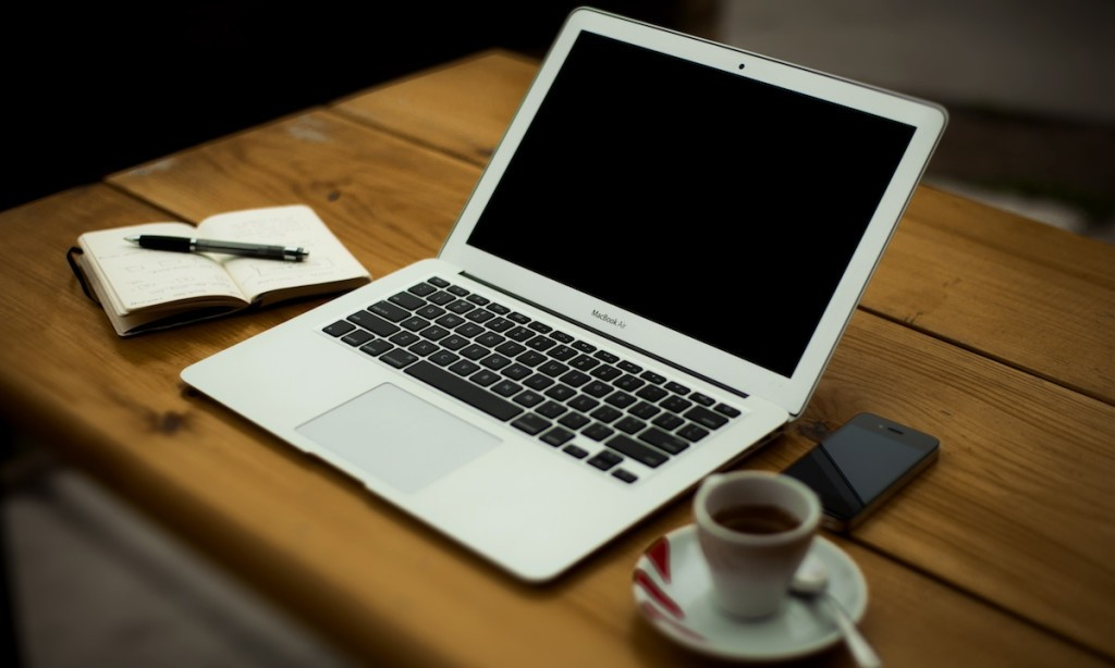 A laptop, coffee, phone and notebook on a table