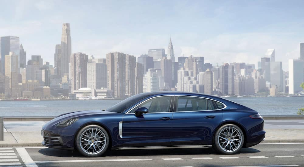 A blue Porsche Panamera 4s on a highway in front of the New York City skyline