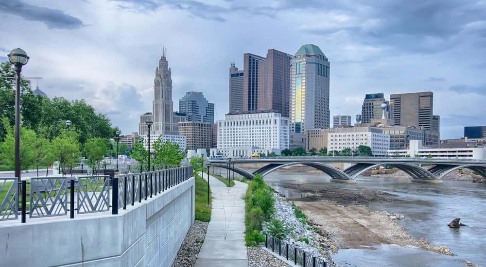 A bridge over a river in Columbus with the skyline against a gray cloudy sky