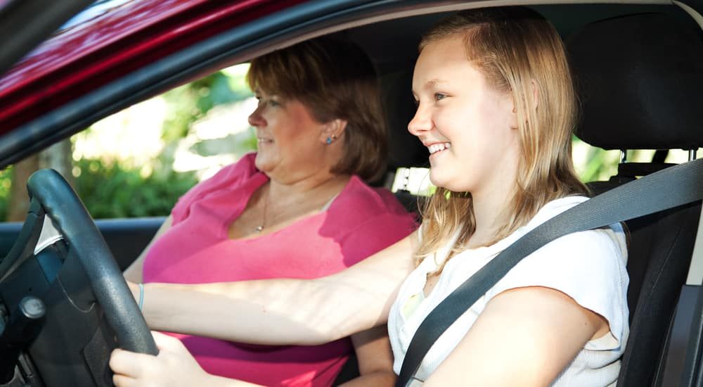 A teen driver practicing driving with her mom