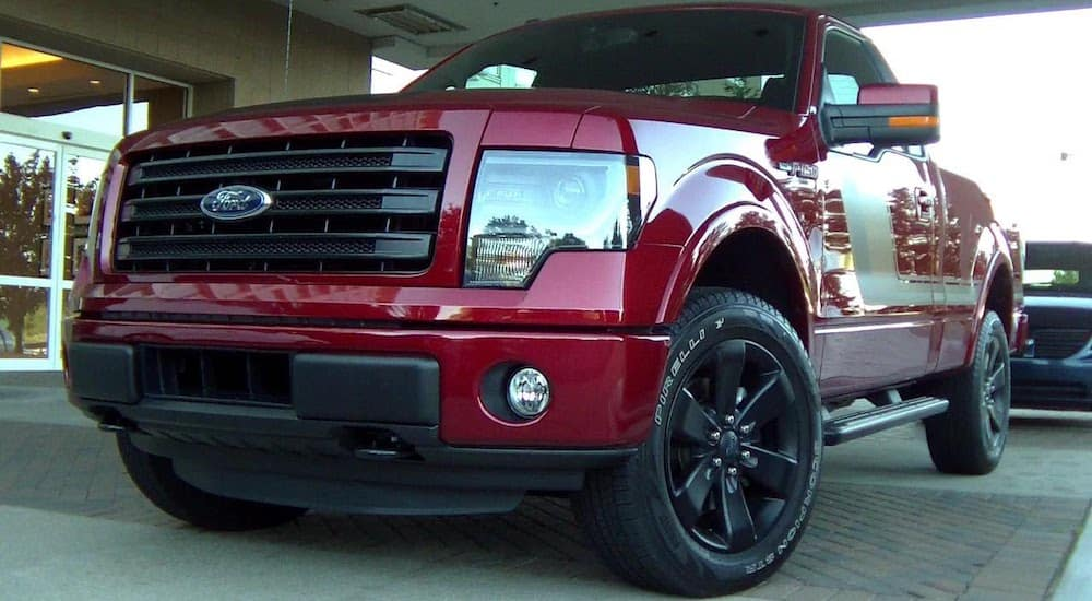 A red Ford F-150 on a dealership lot