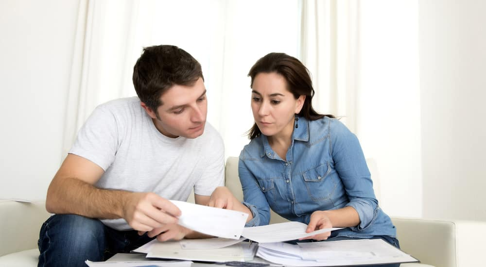 young couple worried at home in stress accounting bank payments in bad financial situation