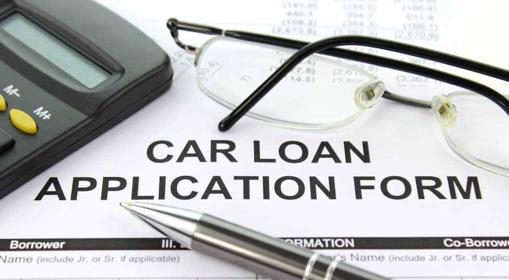 A paper car loan application, glasses, pen and calculator