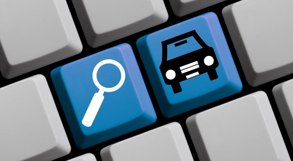 Blue Search and car symbol buttons on gray computer keyboard