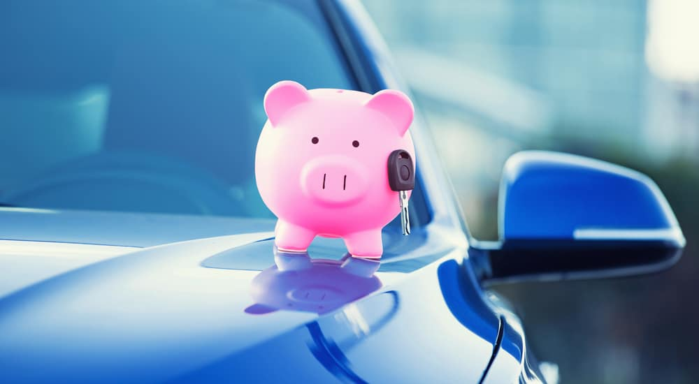 Closeup image new car with piggy bank, key on hood isolated