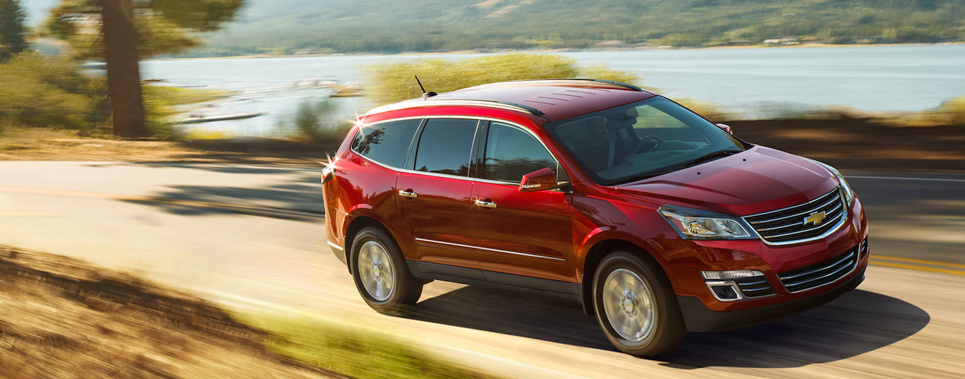 A red 2017 Chevy Traverse cruises down a quite road by a lake