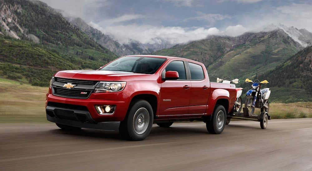 A used red Chevy Colorado with a trailer drives through the mountains