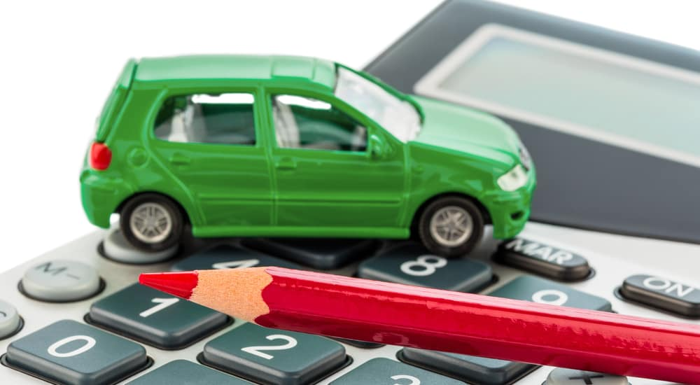 A calculator and green toy car symbolizing the question of auto finance