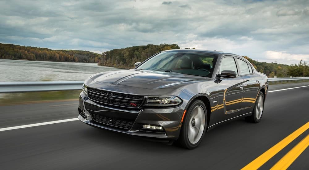 A dark gray used Dodge Charger drives down a coastal highway on a cloudy day