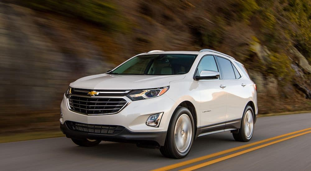 A White Chevy Equinox drives on a mountain road