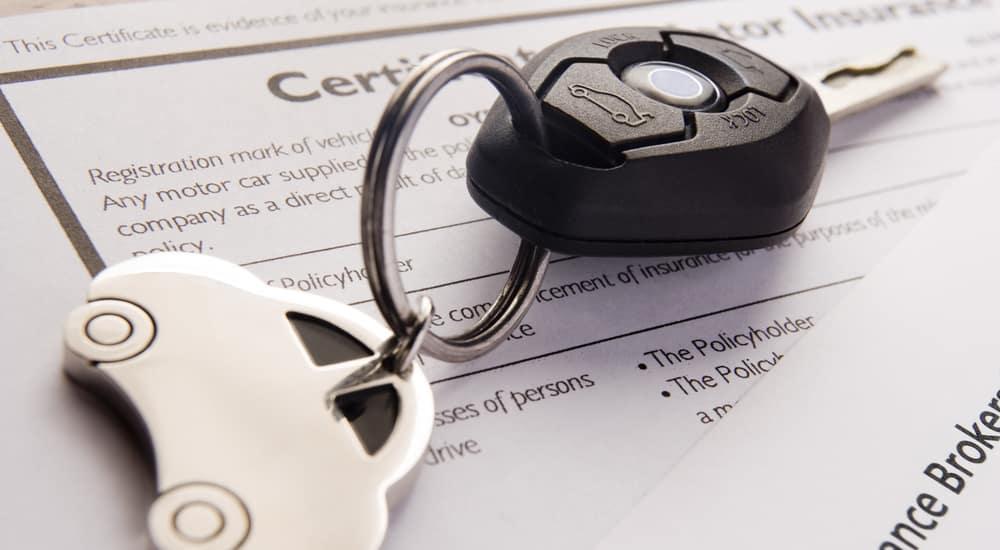 keys on a car loan and insurance document