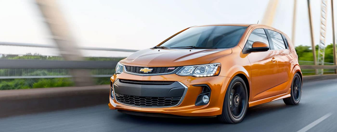 A bright orange 2017 chevy Sonic, which is a popular used Chevy in Columbus, OH, is driving over a steel bridge