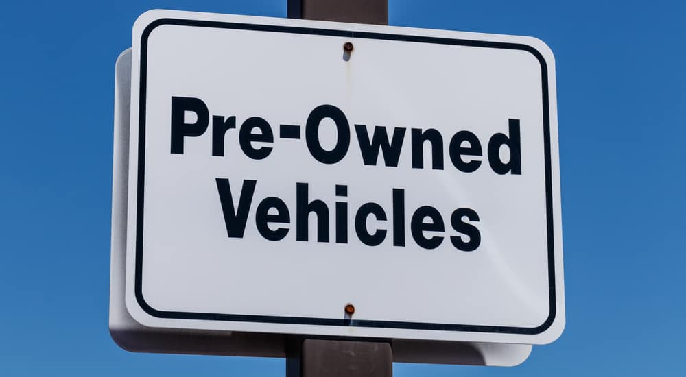 A white sign with blue lettering showing the location of used vehicles