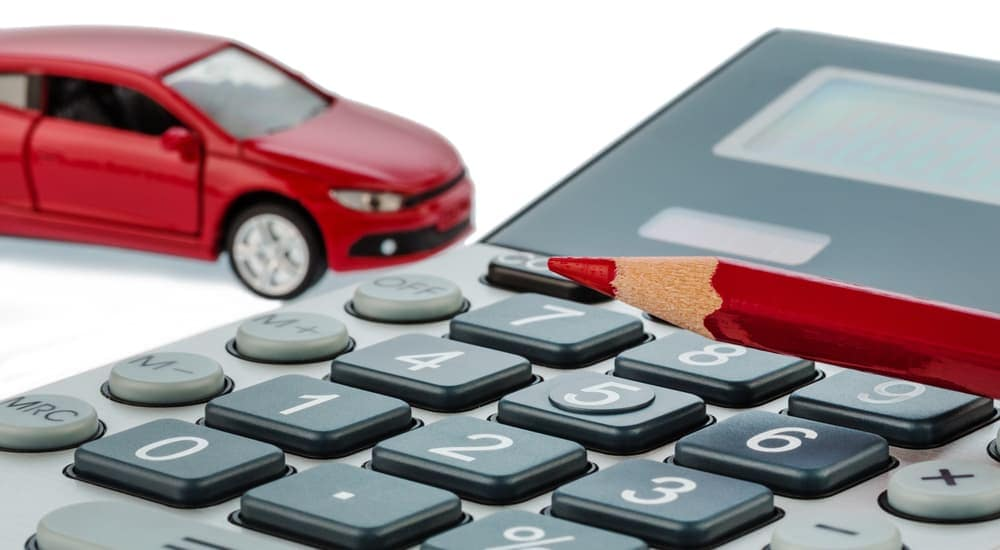 Closeup of calculator with red pencil and red toy car in background, on white