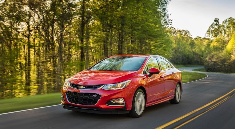 A red Chevy Cruze from an online car dealer travels a tree lined road