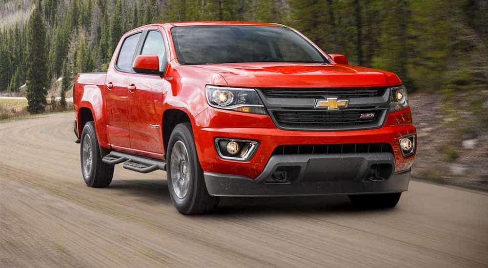 A red 2016 Chevy Colorado races down a dirt pine tree lined road