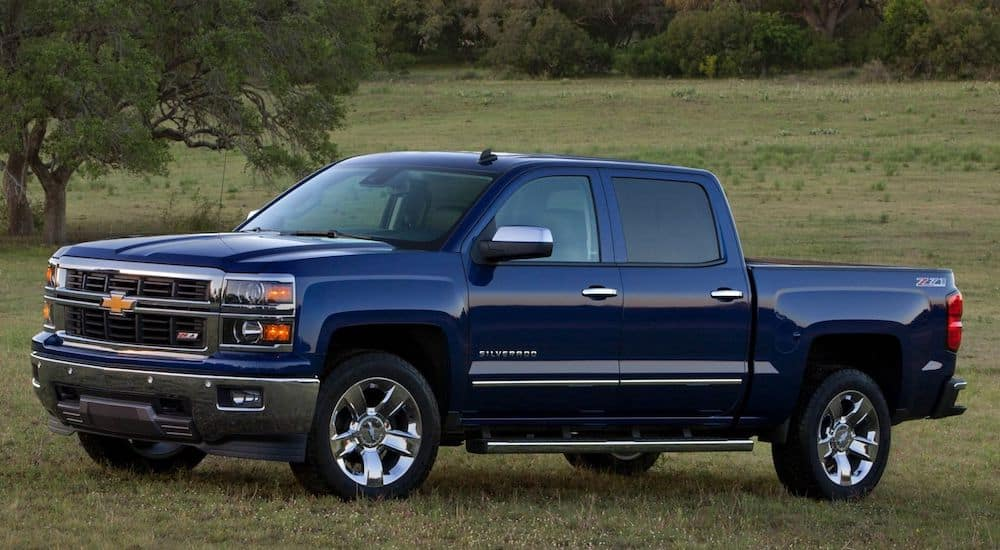 A deep blue 2015 Chevy Silverado in a green field