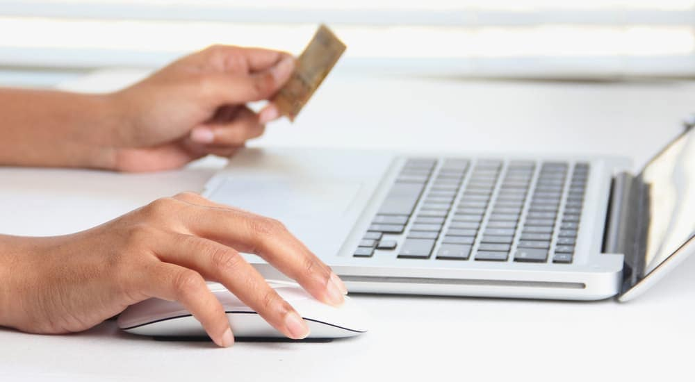 Hands on a mouse and credit card while shopping for used cars in Indianapolis online