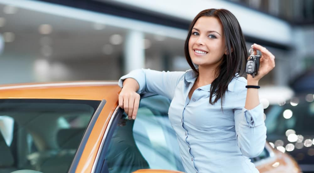 A young women gets her used car online with a no credit car loan