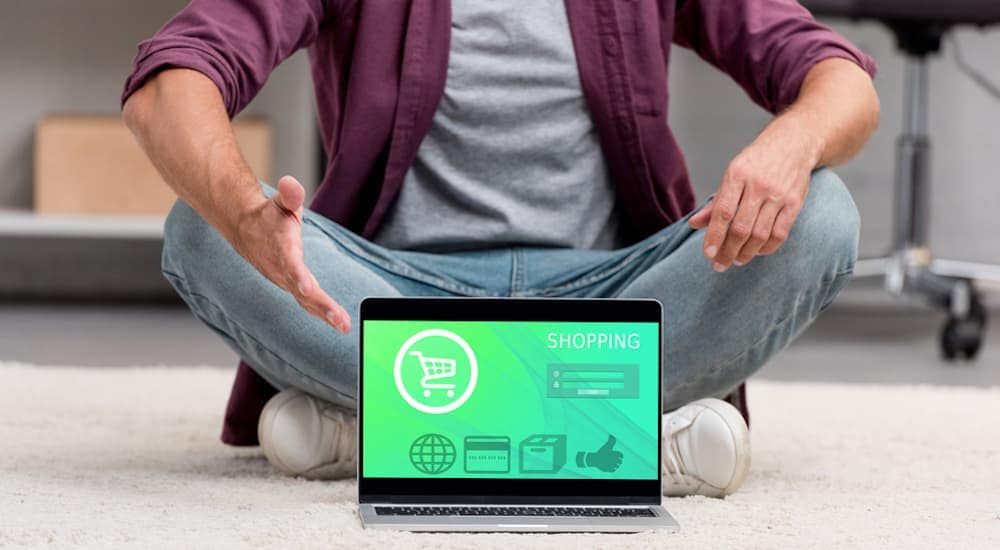 A man sits with a laptop to shop online for cars