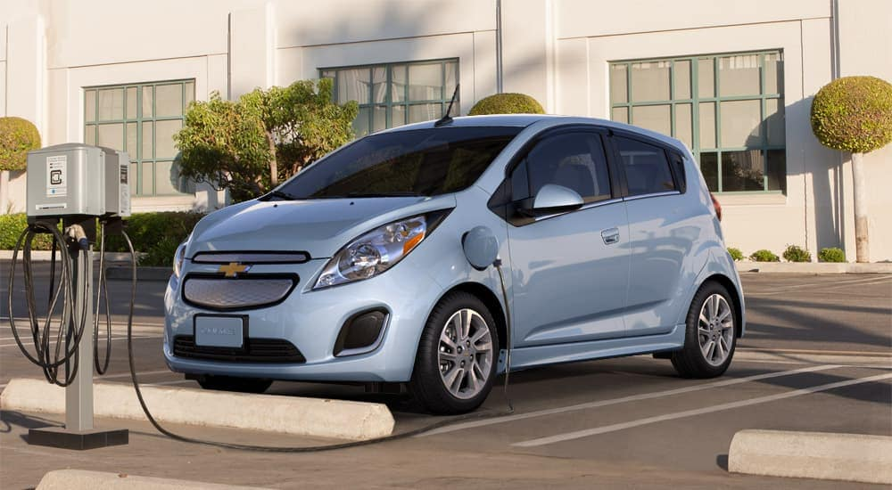 A blue Chevy Spark is charged at a used Chevy dealer in Columbus Ohio