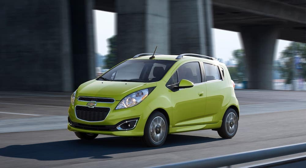 A green Chevy Spark EV travels a local Columbus highway