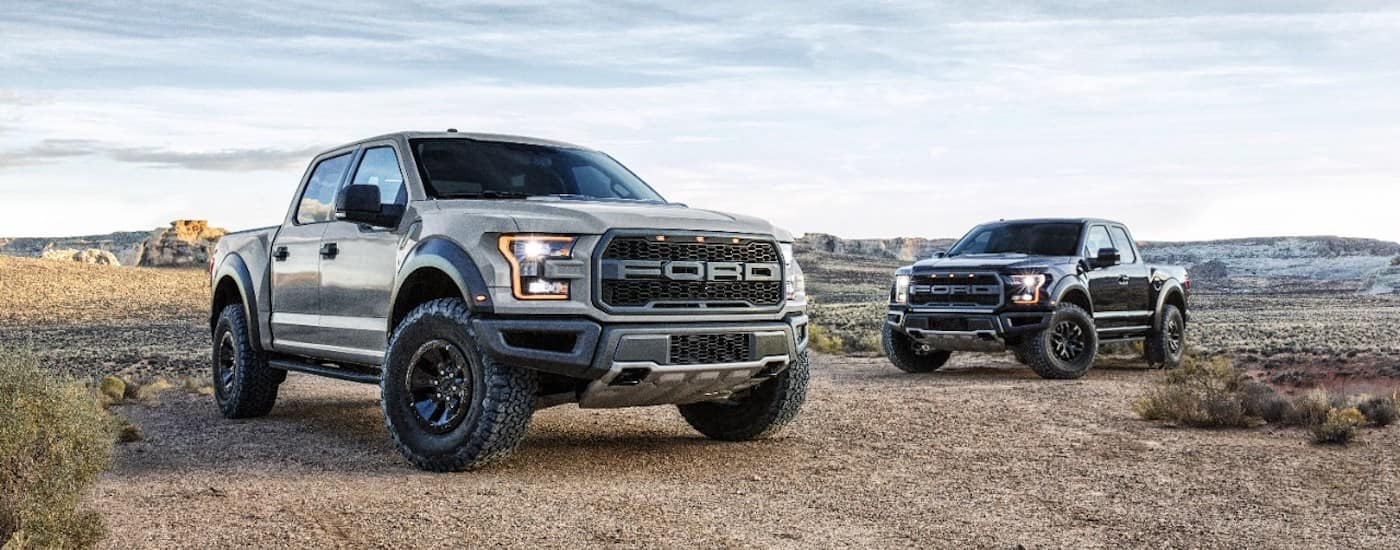 Two 2017 Ford Raptors are parked in a desert with aggressive styling.