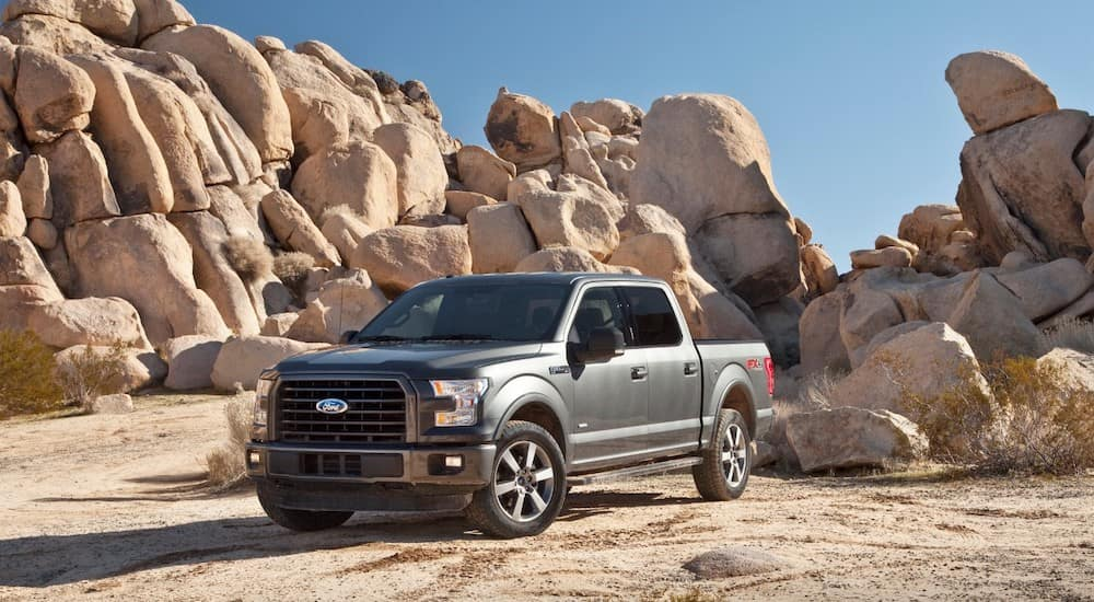 A grey 2015 Ford F-150 is parked in front of desert rocks. When searching used Ford trucks, Columbus, Ohio is a great place to look.