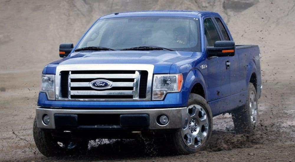 A blue 2009 Ford F-150 in a large dirt pit