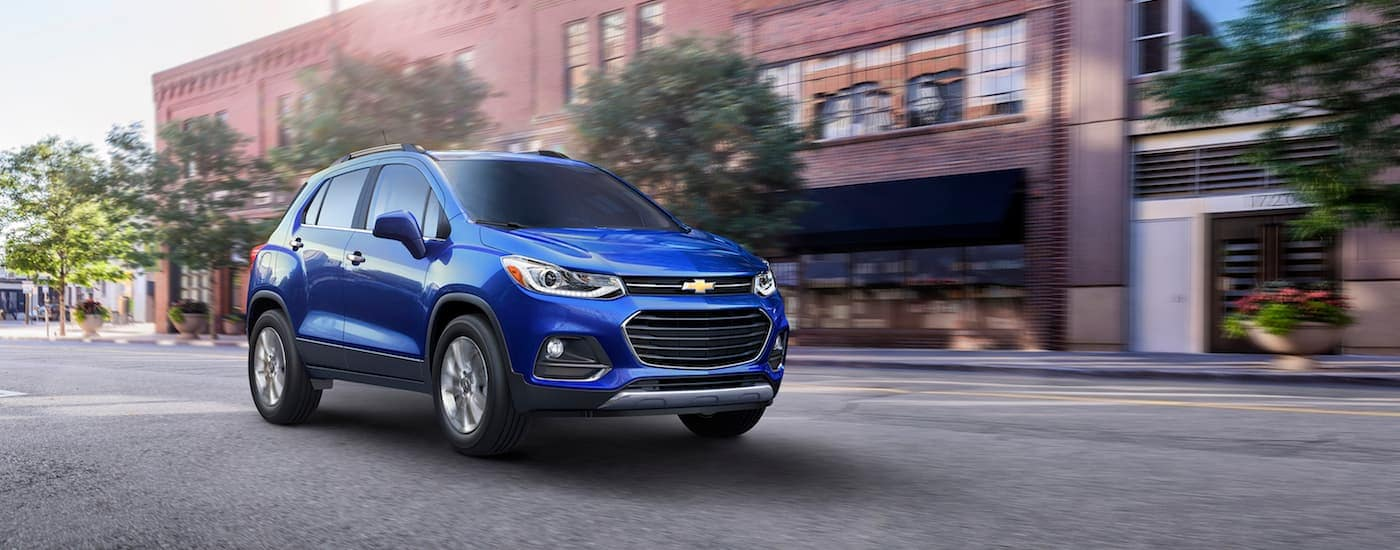 A blue 2016 Chevy Trax on a city street, one of the many Used Chevy SUVs for Sale in Indianapolis