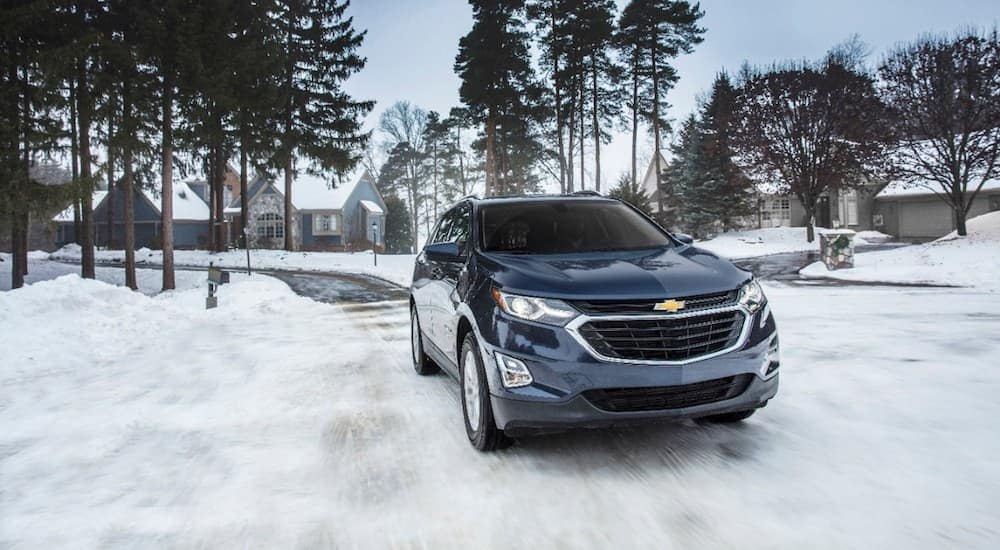 A dark blue 2018 Chevy Equinox drives through the snow, one of many Used Chevy SUVs for Sale in Indianapolis