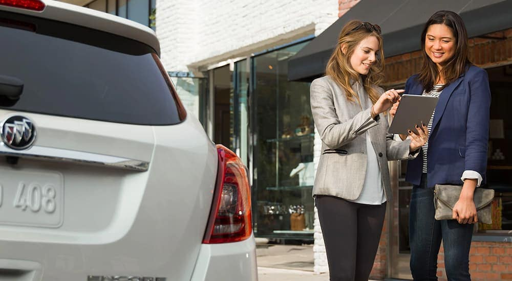 Two young women are standing next to a Buick Encore while looking up Online.cars on a tablet as an alternative to buy here, pay here in Indianapolis, IN.