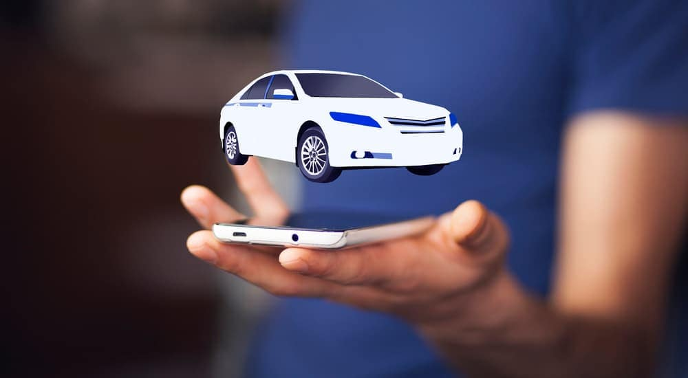 A virtual car is hovering over a man's hand holding his cell phone after looking up alternatives to Buy Here Pay Here in Indianapolis.