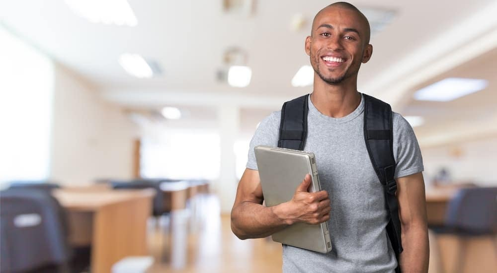 A male college student is holding his laptop and smiling.