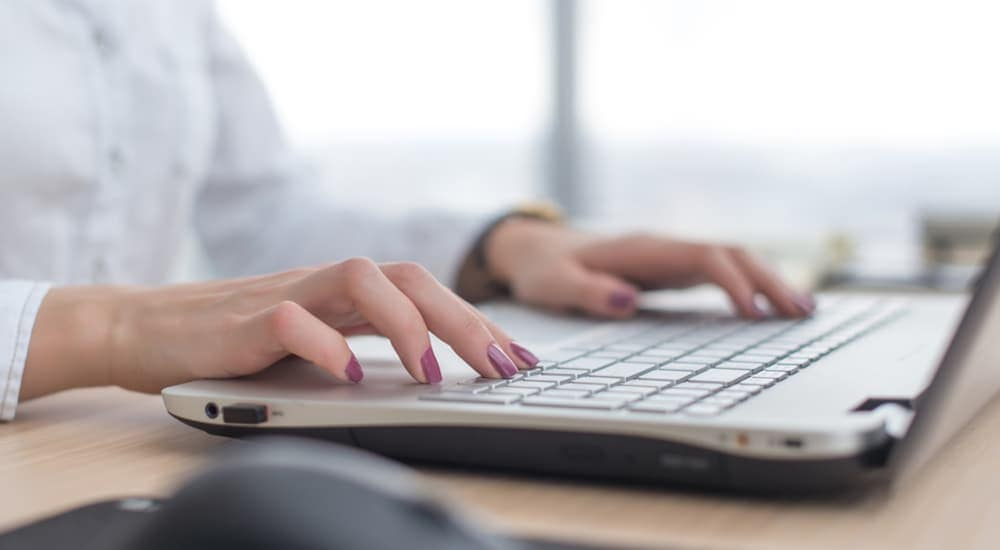 A woman's hands are shown typing on a laptop.